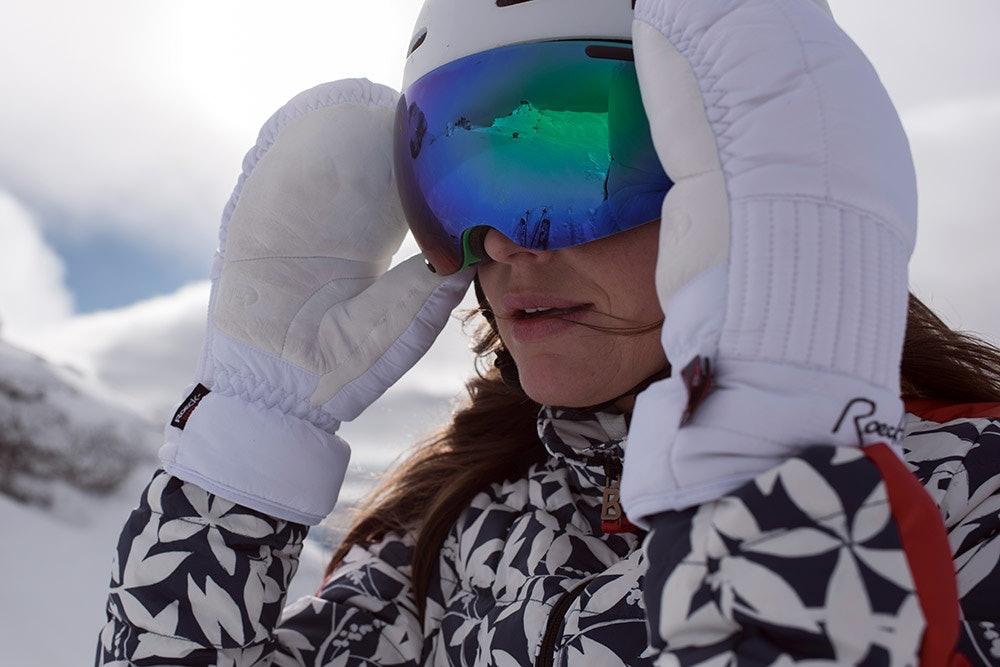 Frau mit sphärischer Skibrille in den Bergen