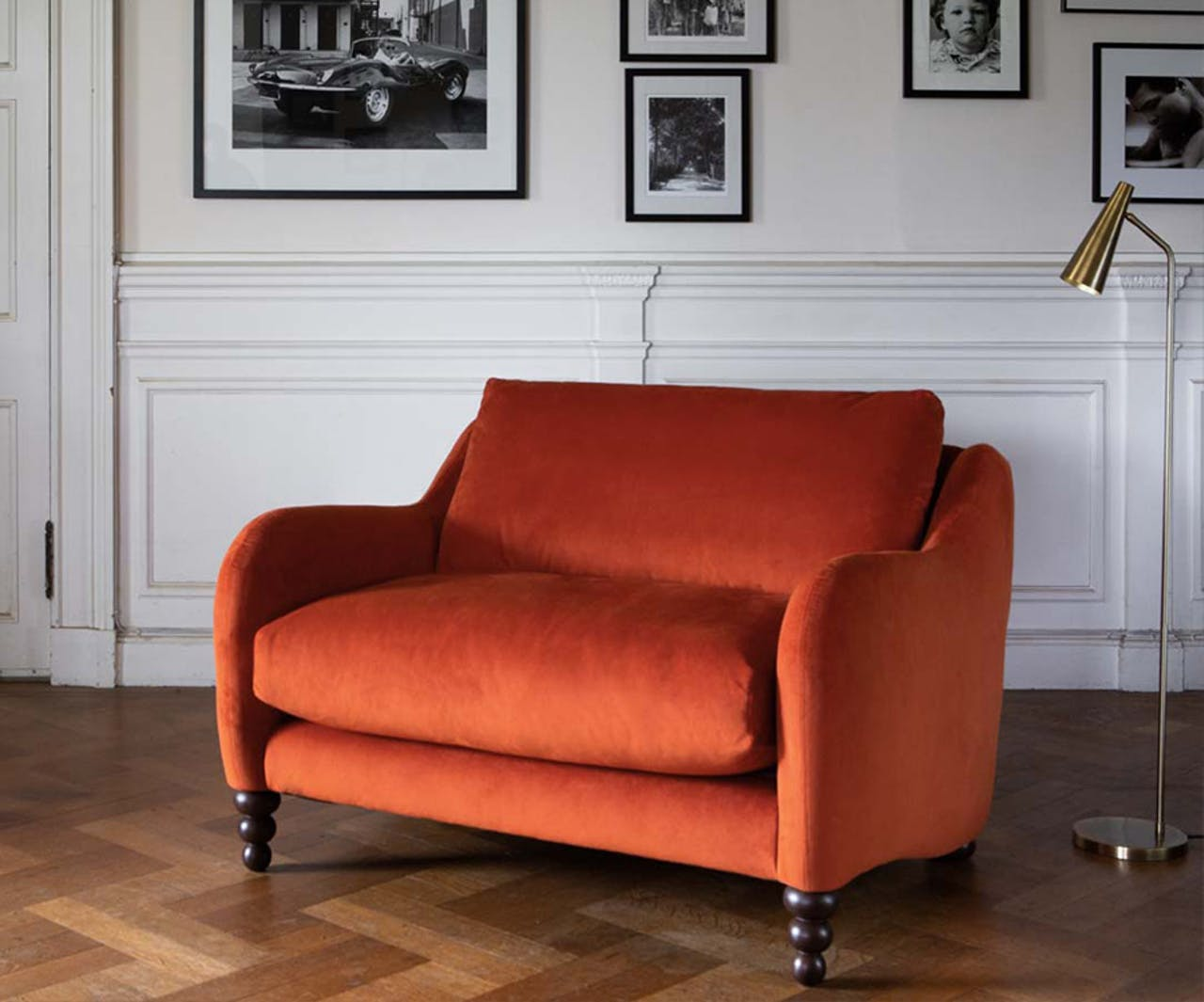 Orange Velvet Love Seat in front of picture wall
