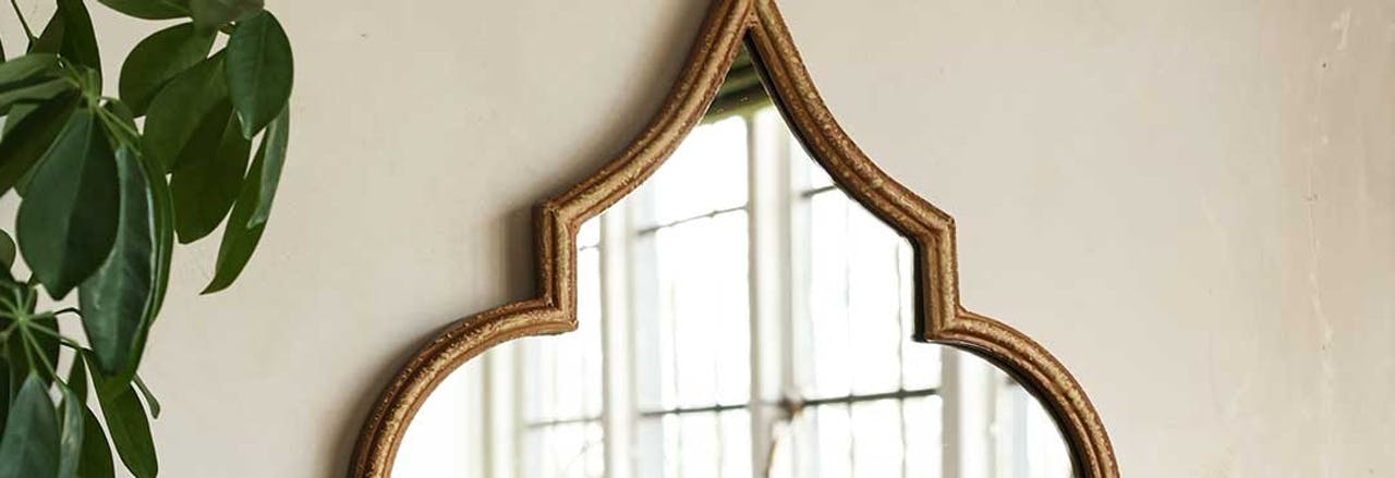 quirky abstract shape wall mirror with gold frame on white wall