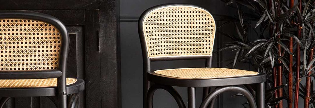 rattan black and natural bar stool in front of bar