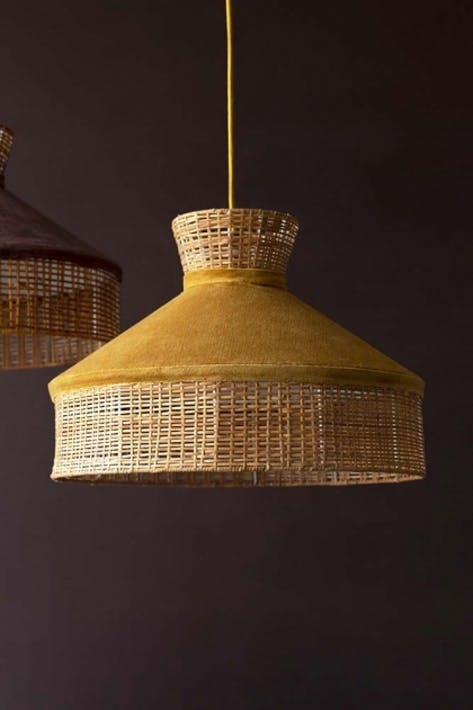 Close-up lifestyle image of the Gold Mustard Velvet & Rattan Pendant Ceiling Light on a dark brown wall background