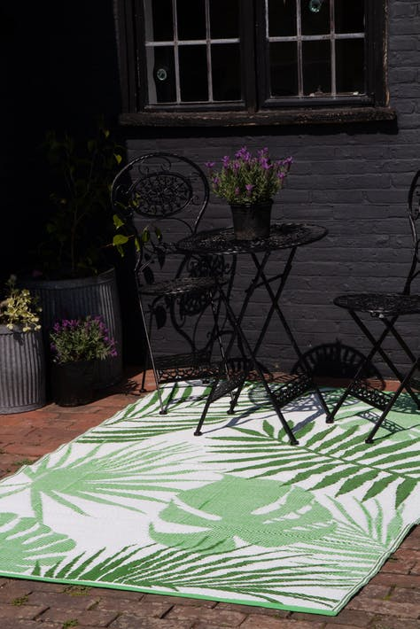 Lifestyle image of the dark side of the Lime Green Tropical Pattern Reversible Outdoor Garden Rug