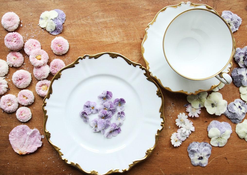 Weißes Porzellan mit goldenem Rand auf einem Holztisch. Lila, weiße und pinke Blumen liegen auf dem Tisch und einem Teller.