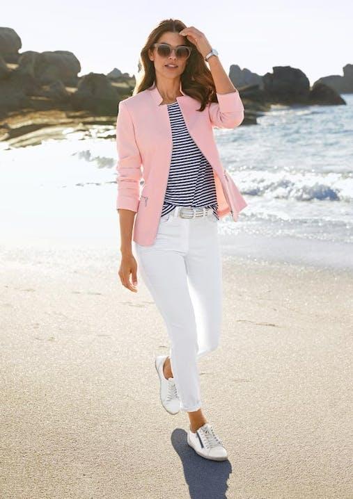Frau geht am Strand mit Sonnenbrille. Sie trägt einen pinken Blazer, ein gestreiftes Shirt, weiße Hose und Sneaker.