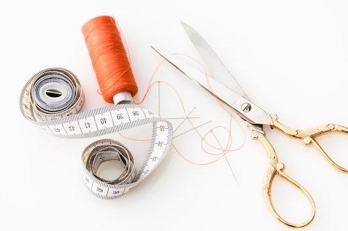 Maßband, orangenes Garn, Nähnadeln und eine Schere mit goldenem Griff liegen auf einem weißen Grund.