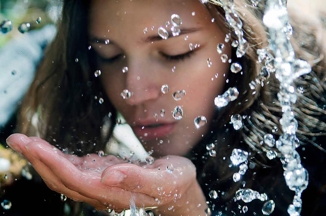 Woman's face close-up, dark brown hair, splashing her face with water. Camera has captured the waterdrops in mid-air.