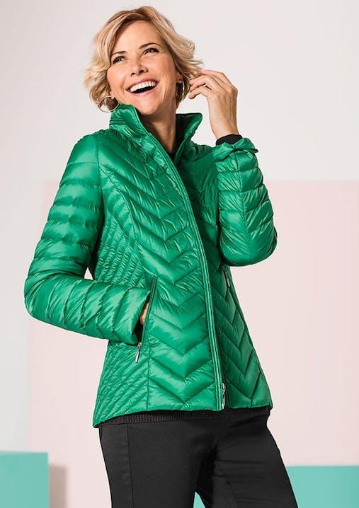 Lachende Frau in froschgrüner Steppjacke.