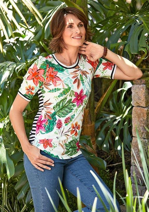 Frau in Jeans und Shirt mit Blumenmuster lehnt mit einem Arm an einer Steinmauer. Im Hintergrund sind Palmen.