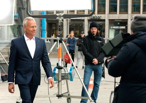 Mann im weißen Hemd und blauen Anzug läuft vor Scheinwerfern her.