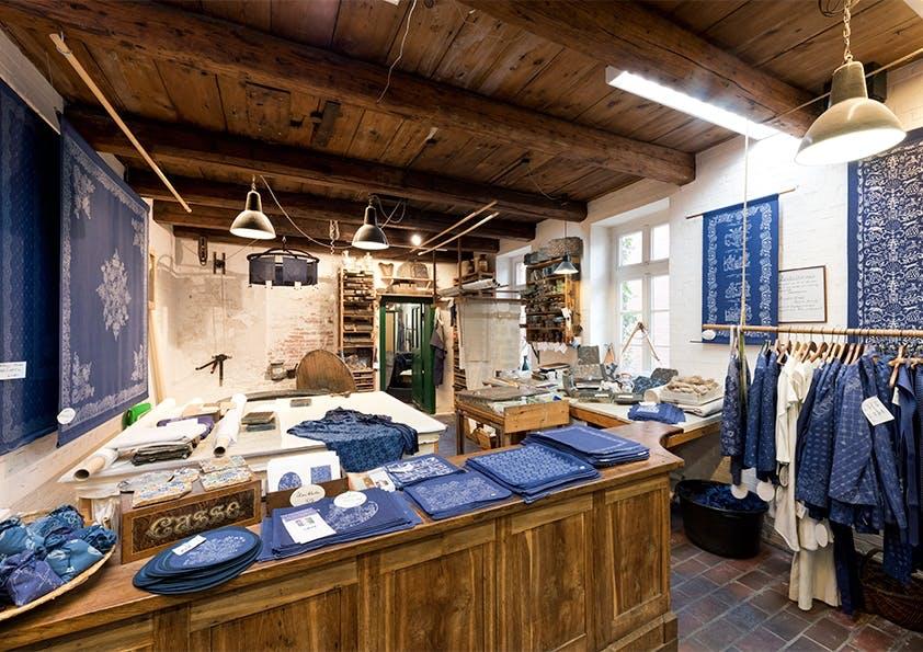 Raum mit Holzdecke und Theken, auf denen blaue Stoffe liegen.