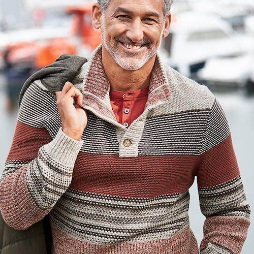 Mann mit gestreiftem Pulli lächelt in die Kamera und hat eine Jacke über die Schulter geworfen.
