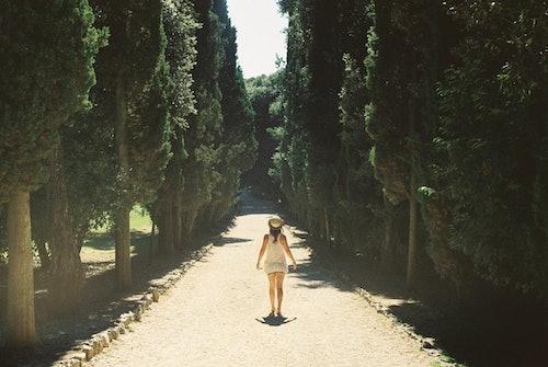 Selin kameraan oleva nainen kävelee pitkää hiekkatietä, jota reunustavat korkeat puut.