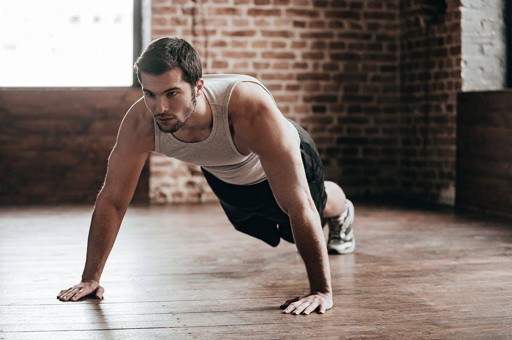 Junger Mann in Hand Plank Position