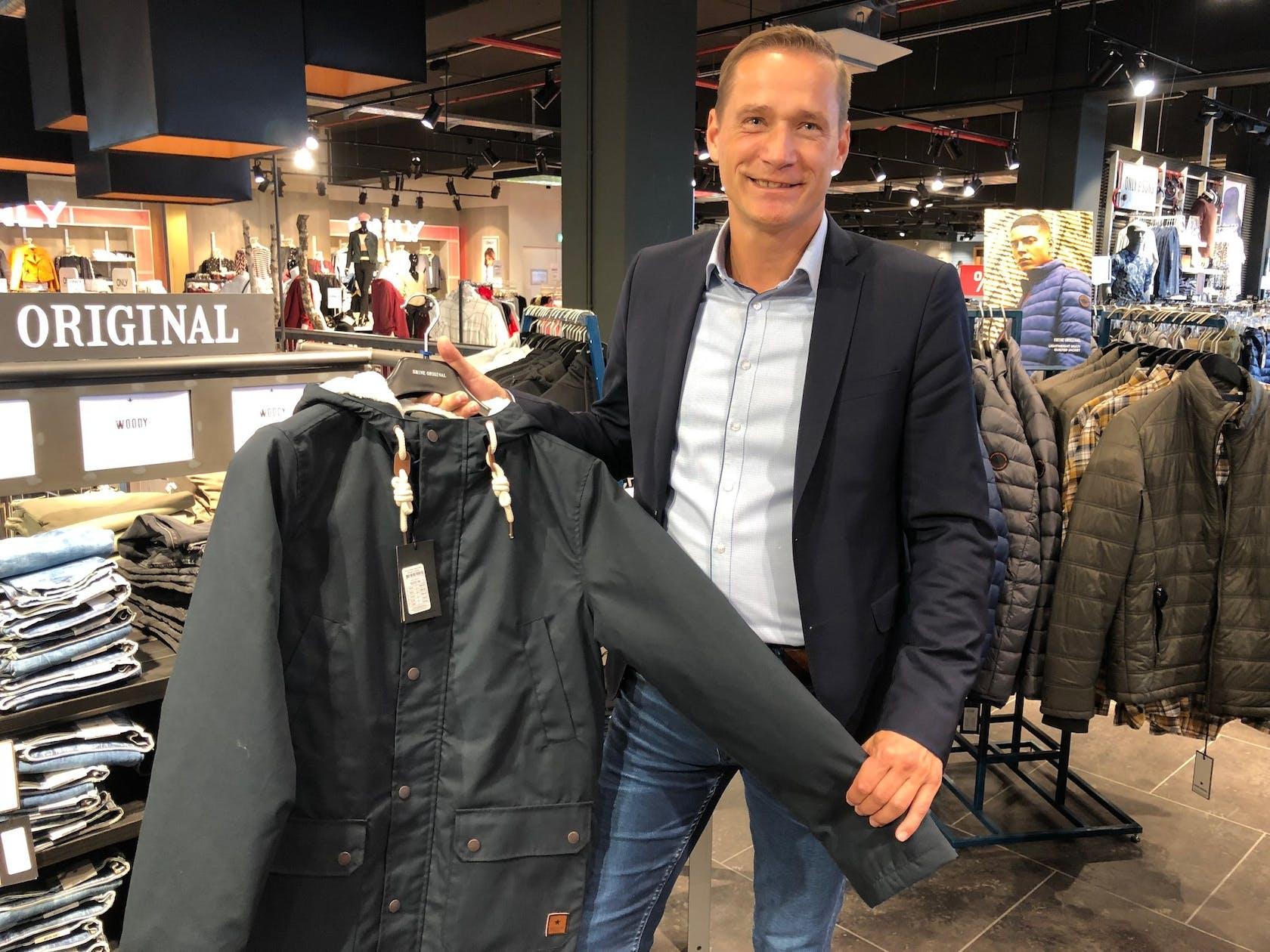 Mann steht vor Kleiderständer mit Jacken und hält eine dunkelblaue Winterjacke in der Hand