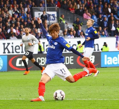 Masaya Okugawa vom Fußballverein Holstein Kiel schießt den Ball