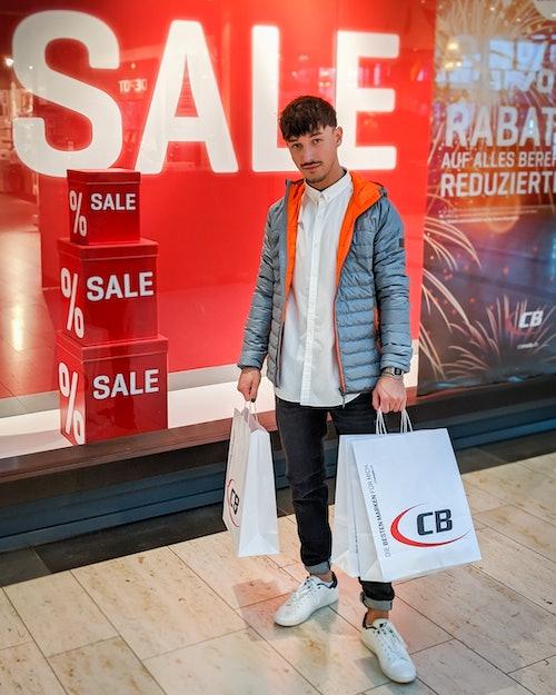 Mann steht in stylischem Outfit und CB-Tüten in der Hand vor Modegeschäft