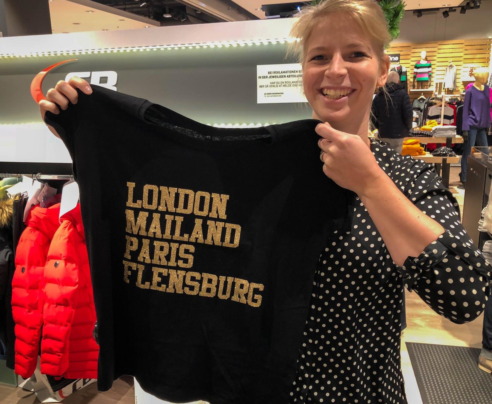 junge Verkäuferin hält T-Shirt hoch