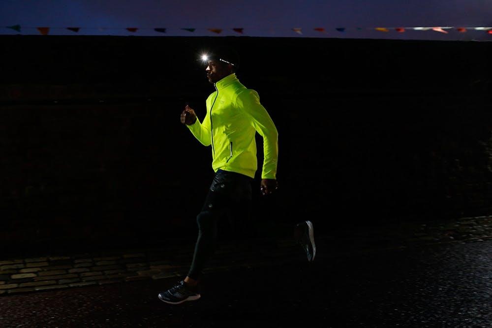 Mann läuft im Dunkeln mit Stirnlampe