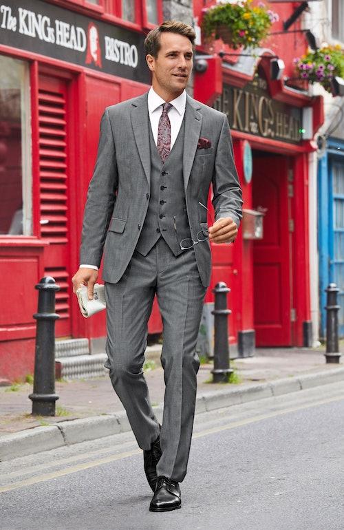 Mann im grauen Anzug mit weißem Hemd und roter Krawatte hält eine Zeitung und eine Brille in den Händen.