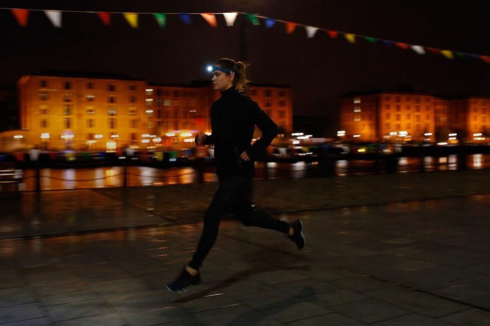 Läuferin im Dunkeln mit Stirnlampe
