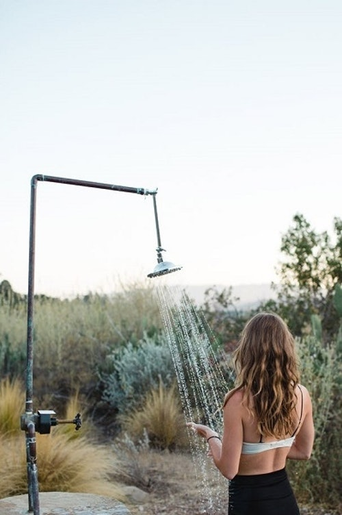 En kvinde tager et udendørs bad med ryggen til kameraet. Hun er omgivet af grønne buske og en klar himmel.