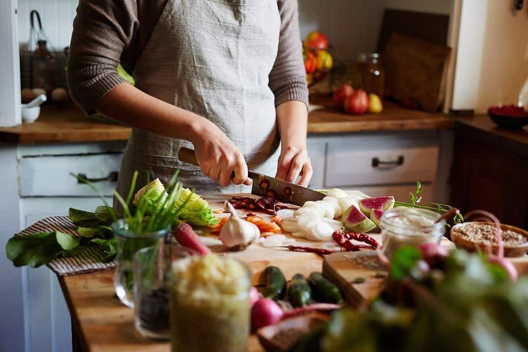 Nainen, jolla on pellavaesiliina yllään, seisoo keittiössä pilkkomassa erilaisia tuoreita ja värikkäitä vihanneksia.