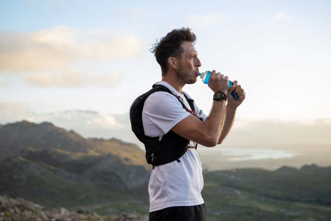 Mann trinkt in Gebirgsumgebung, mit Garmin Enduro GPS-Multisportuhr