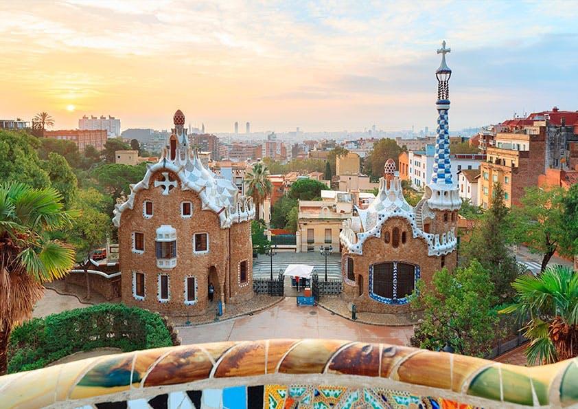 Aussicht von einer bunten Mauer aus auf eine Stadt mit Palmen, Kirchen und vielen Häusern.