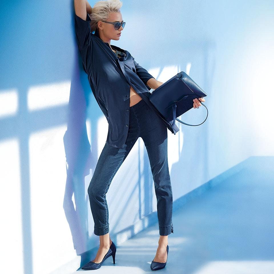 Blonde Frau mit Sonnenbrille in blauem Outfit bestehend aus Bluse und Jeans.
