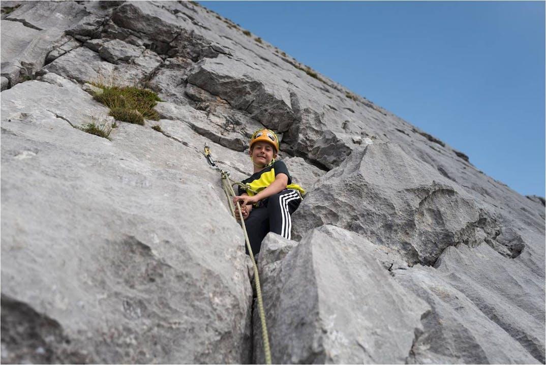 Kind beim Klettern am Fels