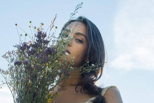 Italialainen nainen, joka pitelee tuoksuvaa villikukkakimppua