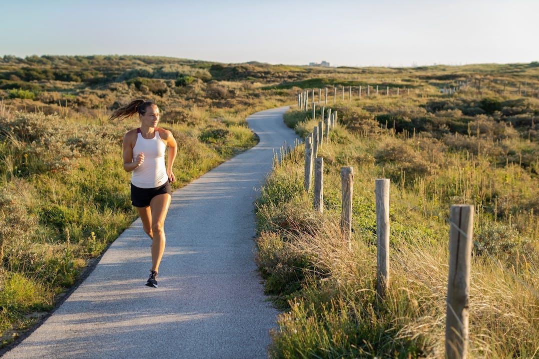 Frau läuft in Hügellandschaft
