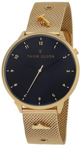 Cette montre THOM OLSON se compose d'un Boîtier Rond de 40 mm et d'un bracelet en Acier Doré