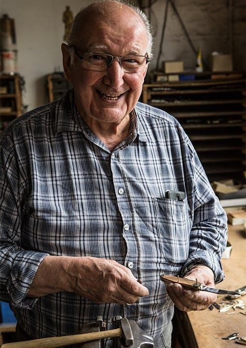 Alter Mann mit Brille und Karohemd hält ein Messer in der Hand und lächelt.