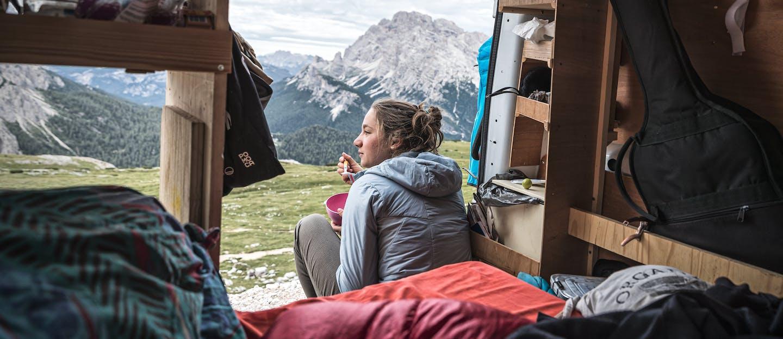 Ragazza che mangia in mezzo alle montagne