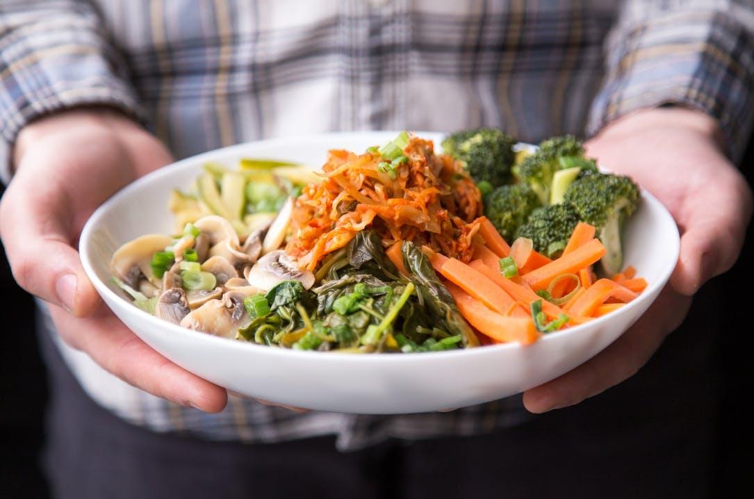 Jemand hält einen Teller gefüllt mit bintem Gemüse