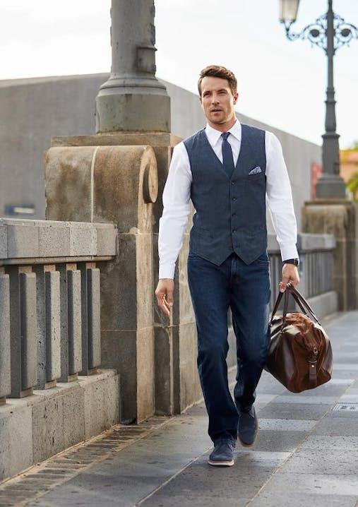 Mann läuft mit einer braunen Reisetasche in der Hand über Steinpflaster. Er hat eine dunkelblaue Jeansweste, weißes Hemd und Jeans