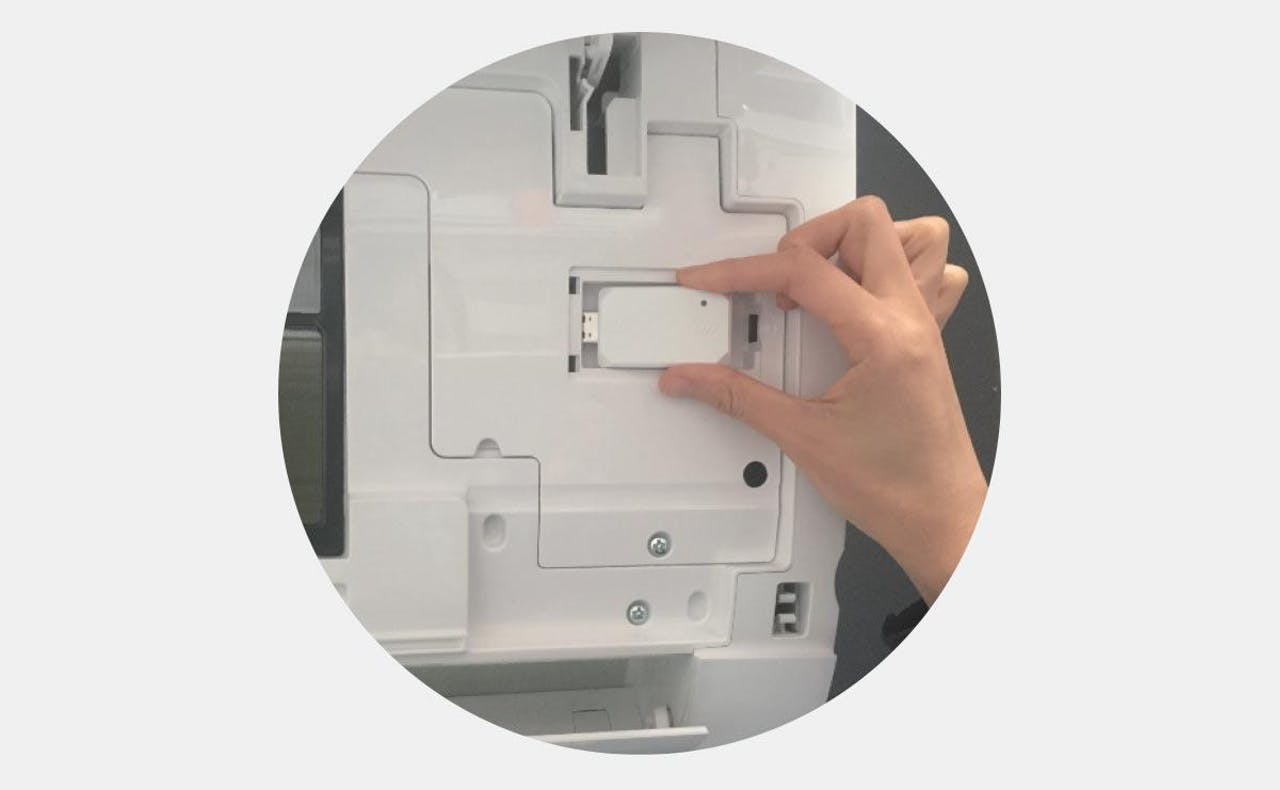 Photo of owner plugging WiFi USB Adapter into ductless wall mounted unit