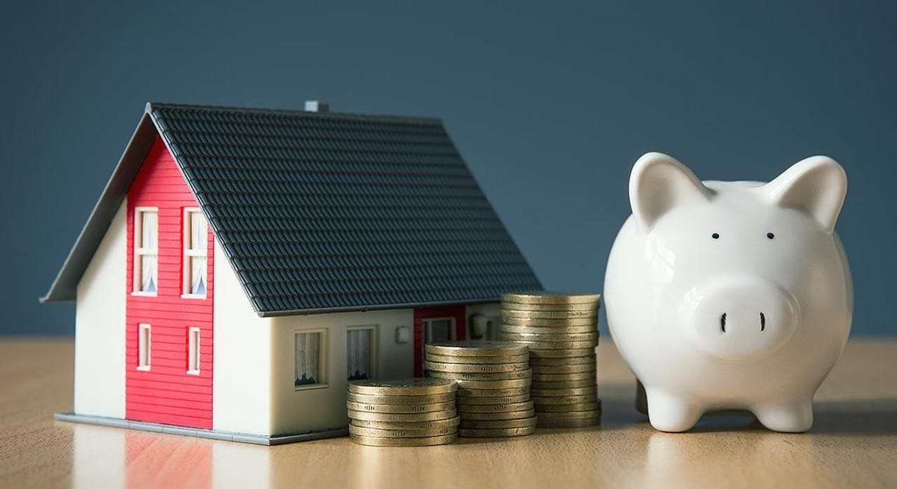 Photo of house and piggy bank showing money savings