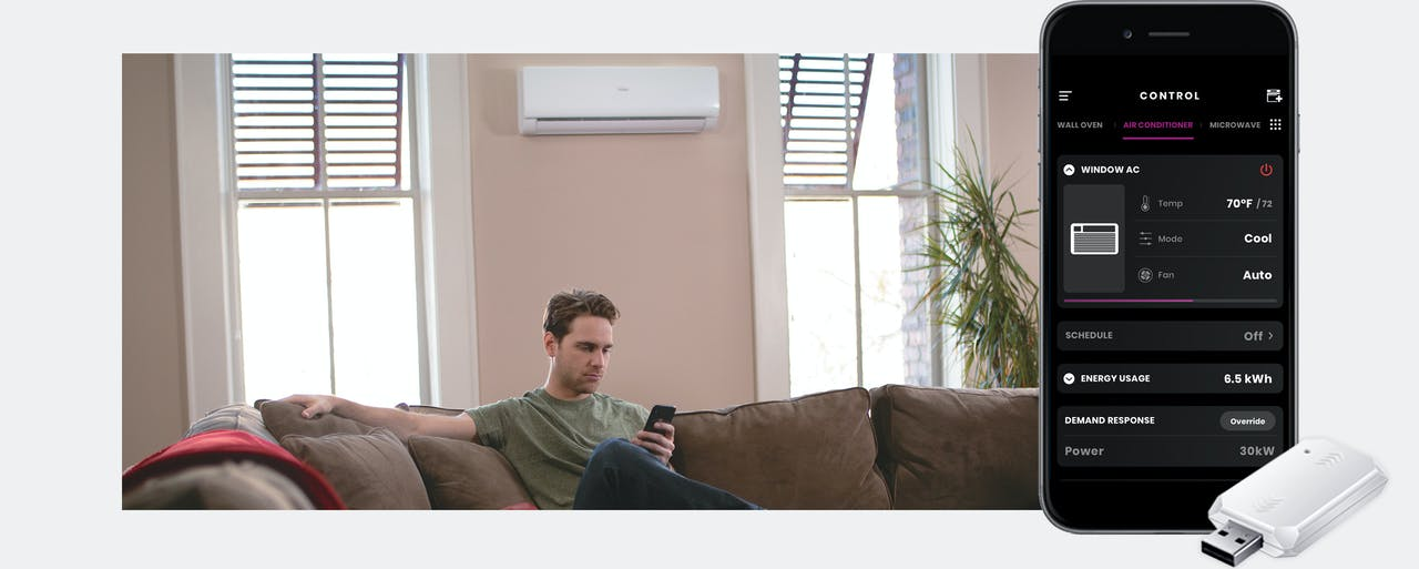 Photo of Haier Ductless Wall Mount Unit installed in living room, guy on couch with phone using app to control unit