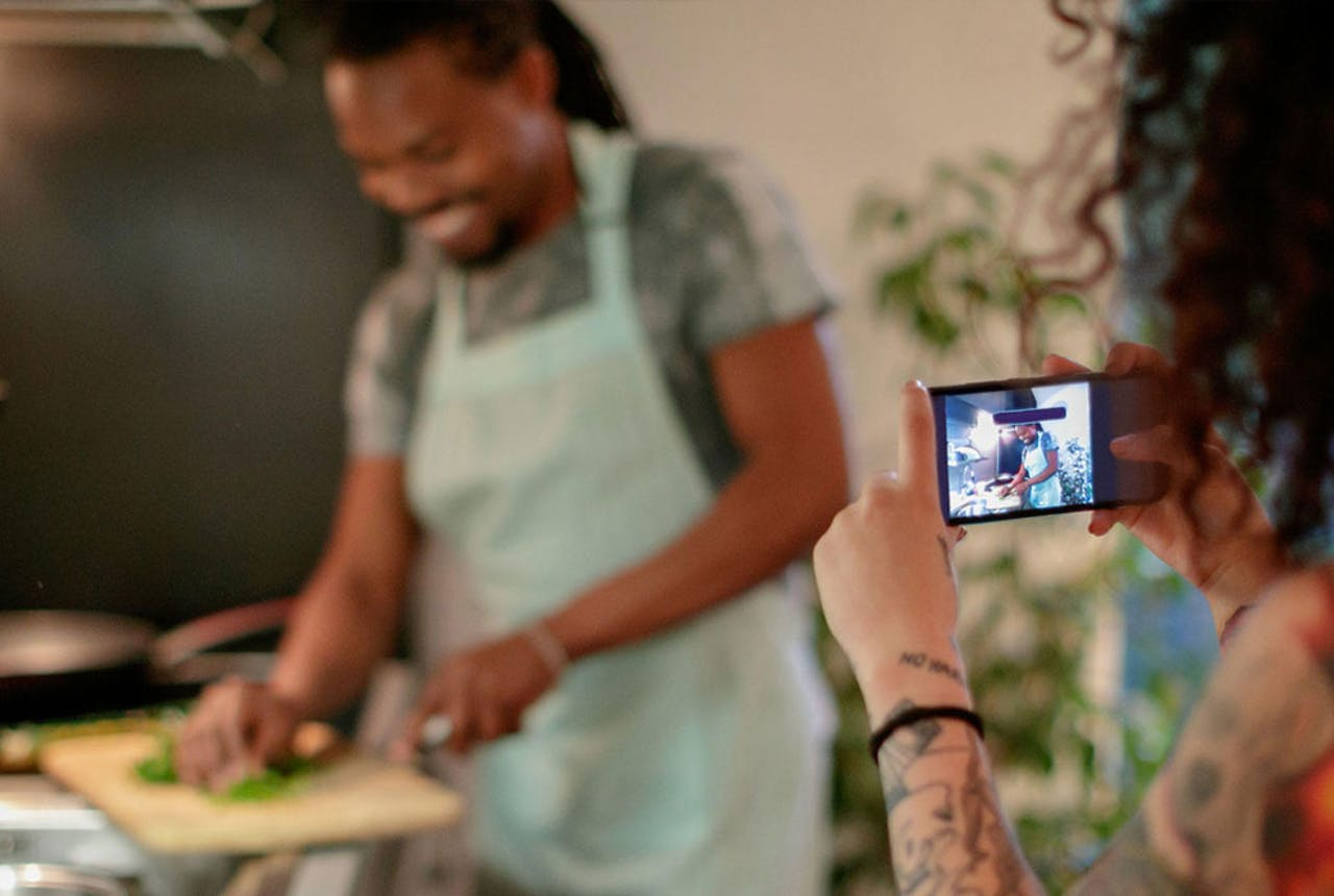 Young couple cooking in kitchen taking pictures