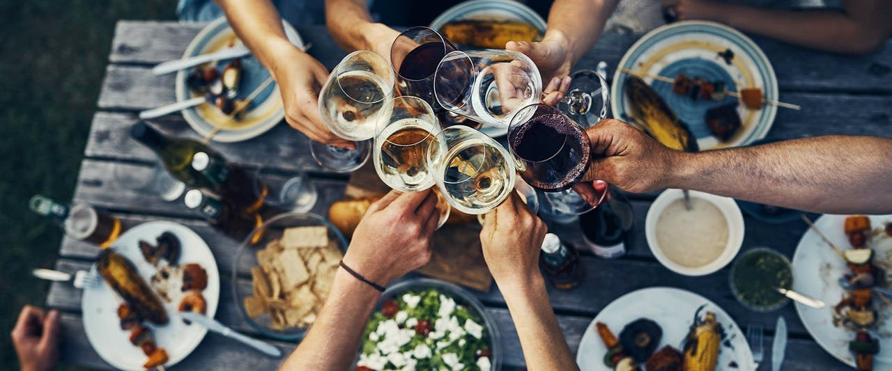 group of friends making a toast over dinner