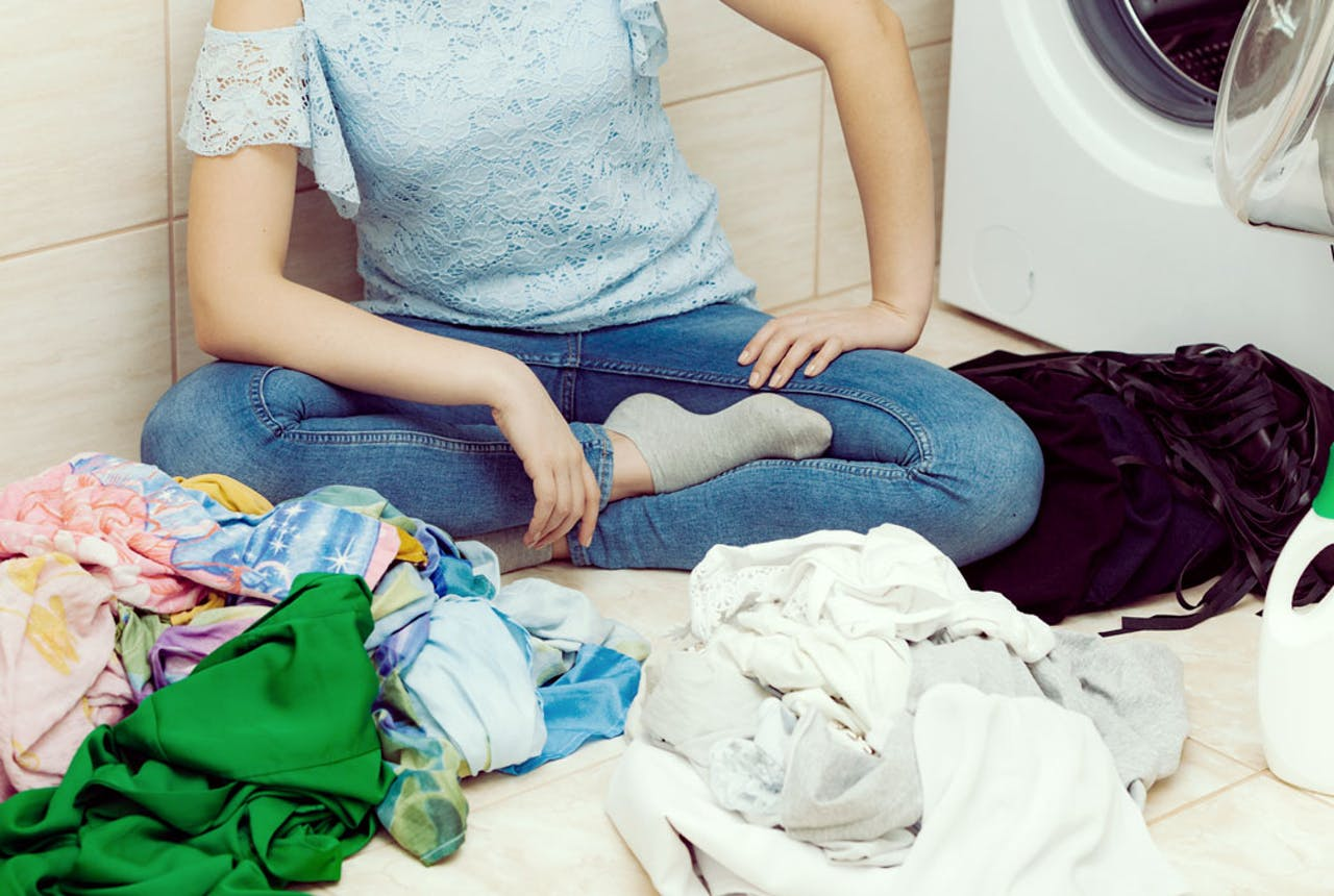 Young woman sorting clothes by colors
