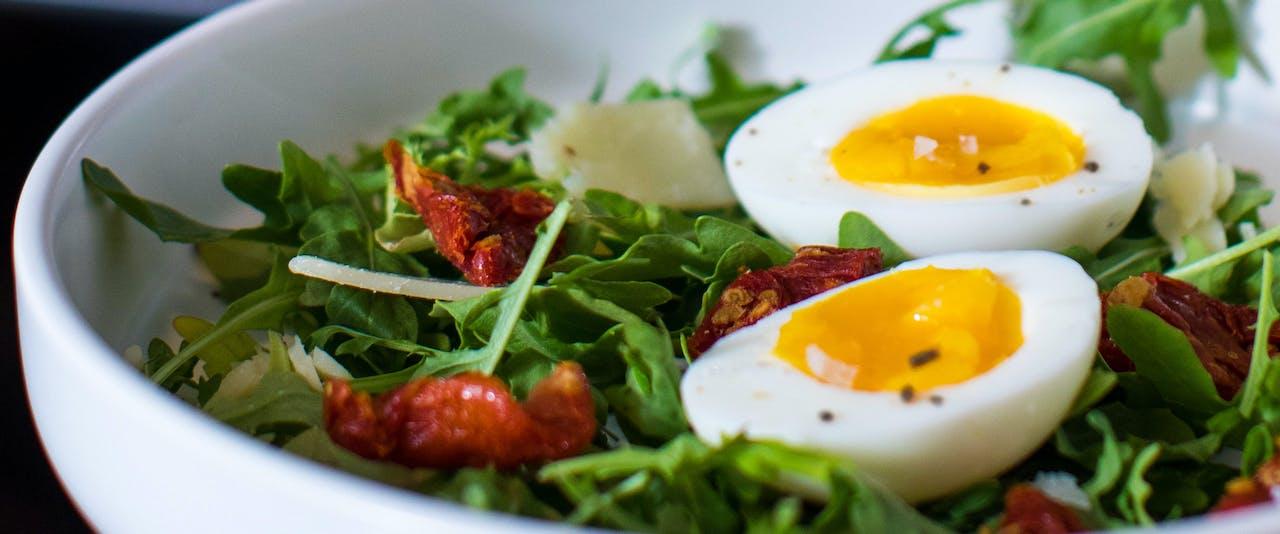 Salad bowl of arugula salad with jammy eggs