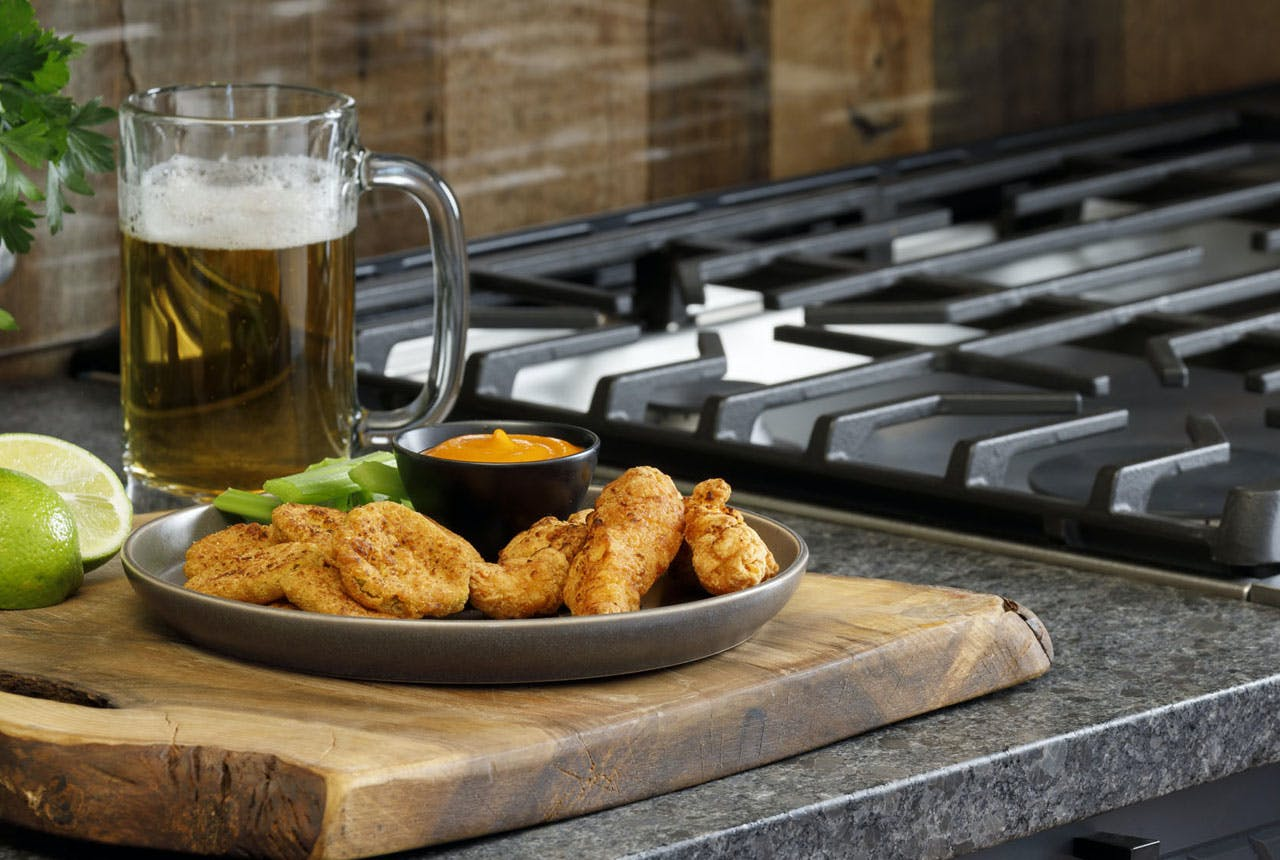 Air Fried Chicken Tenders and fried pickles on a serving platter with a mug of beer