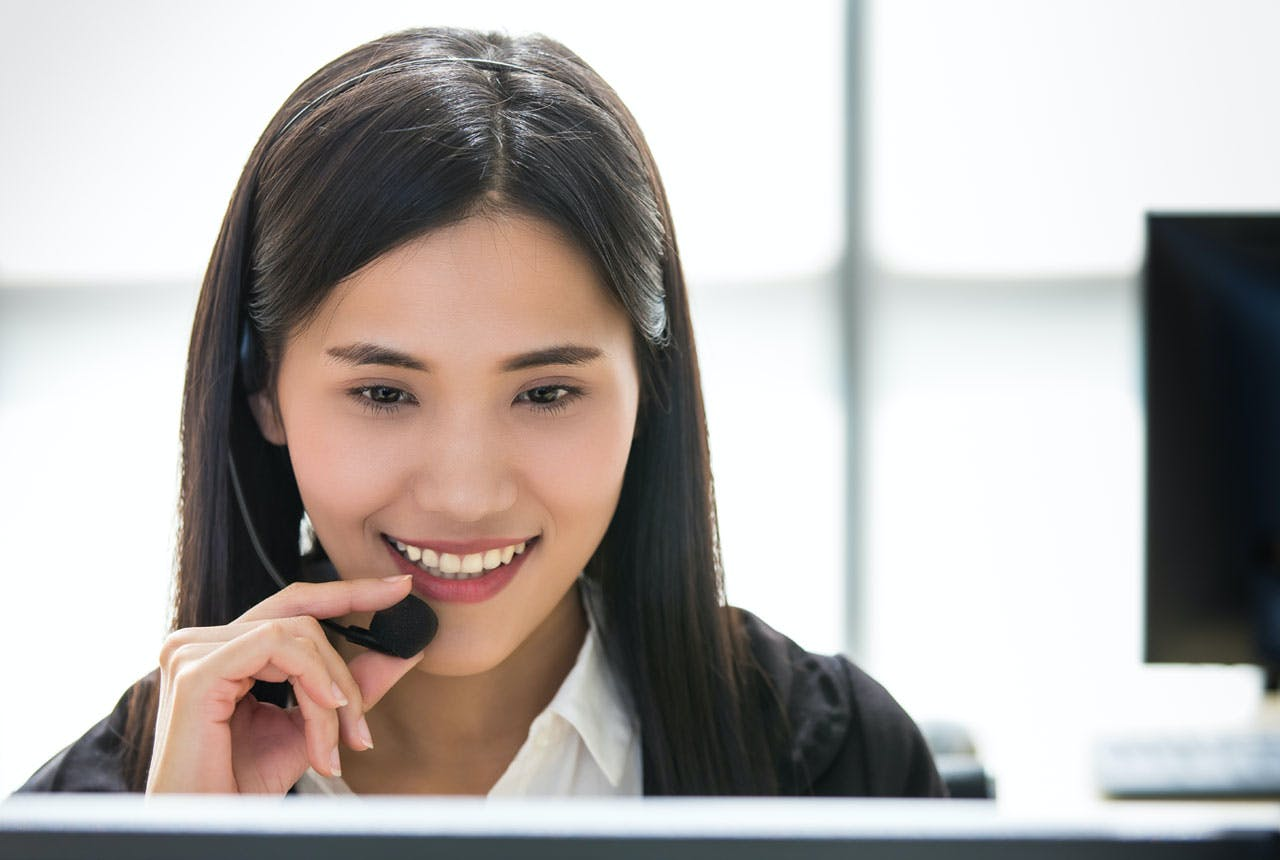 woman call center officer wearing microphone headset and happy working with a friendly face