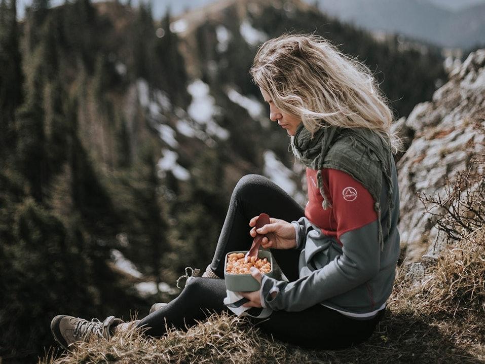 Junge Frau macht Pause beim Wandern