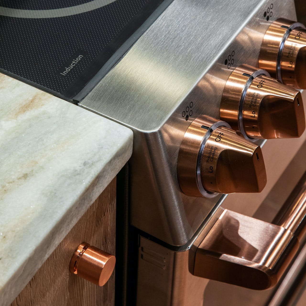 Cafe induction range in stainless with brushed copper hardware