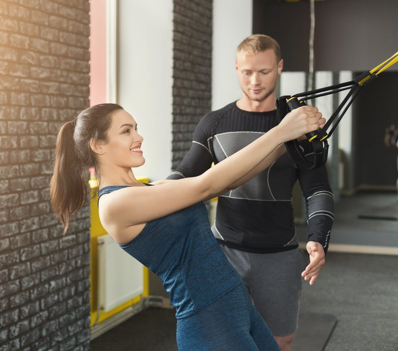 TRX Training Frau mit Trainer