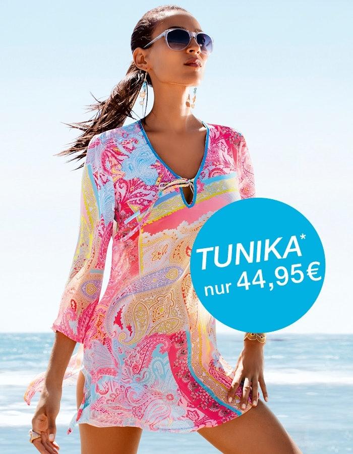 Dame mit Sonnenbrille in einer bunten Tunika gekleidet am Strand